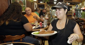 Judith Castro serves a lunch order June 12, 2015 at a local grocery store in the Little Havana area of Miami. (AP Photo: Alan Diaz)