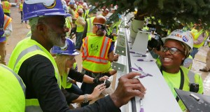 Alan Page, a former Minnesota Viking player, signs the final steel beam to be put in place for the new Vikings stadium Thursday in downtown Minneapolis. Page recently retired from the Minnesota Supreme Court. (Staff photo: Bill Klotz)