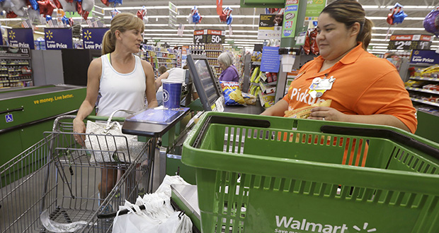 A shopper checks out June 4 at a Wal-Mart Neighborhood Market store in Bentonville, Arkansas. The Federal Reserve said Wednesday that steady consumer spending and an improving housing market spurred modest U.S. economic growth in the late summer. (AP Photo/Danny Johnston)