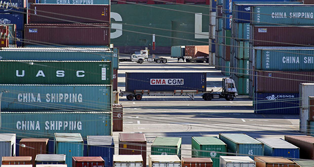 Trucks move containers Feb. 12 at the Port of Los Angeles. The Commerce Department reported Tuesday that the U.S. trade deficit jumped in August. (AP file photo)