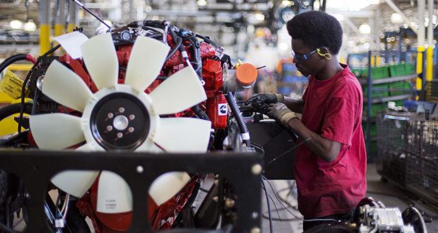 Antwan Devereux works on a school bus engine Sept. 18. 2015 on the assembly line at Blue Bird Corporation's manufacturing facility, in Fort Valley, Georgia. (AP Photo: David Goldman)
