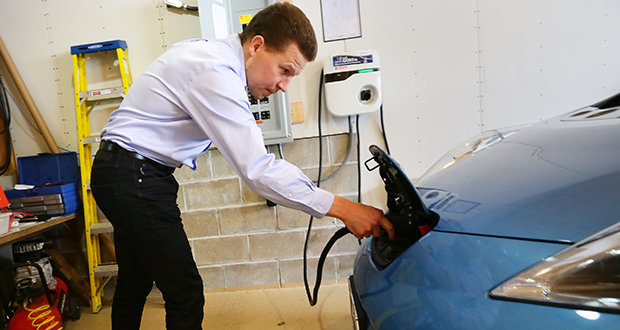 Jukka Kukkonen, founder of PlugInConnect, demonstrates how to plug in his Nissan Leaf electric car in the garage of his Highland Park home in St. Paul. (Staff photos: Bill Klotz)