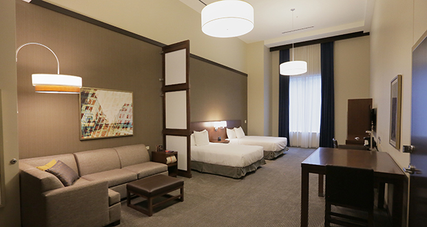 Most rooms in the Hyatt Place like this fourth-floor double queen suite have 13-foot ceilings. The hotel added more furniture and larger televisions to lessen the impact of so much vertical space. (Staff photo: Bill Klotz)