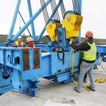 Workers disassembling a segment lifting machine.