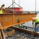 """Concrete being poured for a """"skirt,"""" a decorative element on the sides of the bridge."""