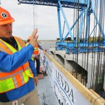 Project Manager Michael Beer explains the process for lifting a concrete segment into place.