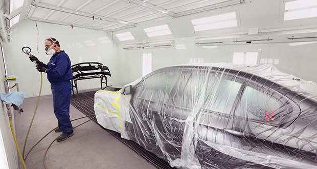 Oscar Auto Body at 2827 First Ave. S. installed a paint booth in 2015 with money from Minneapolis' cost-sharing program. Part-owner Ramin Hakimi says the booth has improved both the indoor environment and the quality of the work. In this photo, employee Boyd Frazier applies a layer of water-based clear coat in the new paint booth. (Staff photo: Bill Klotz)