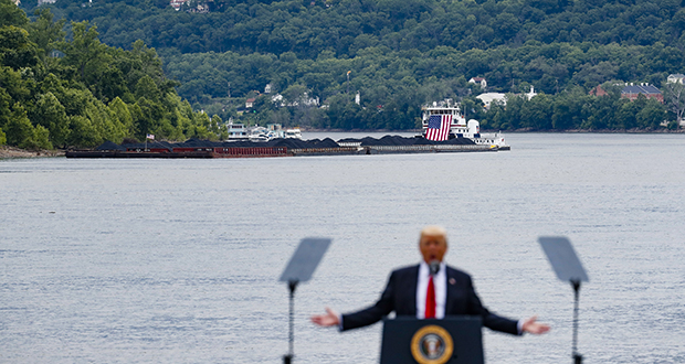 A coal barge is positioned as a backdrop behind President Donald Trump as he speaks June 7 during a rally at the Rivertowne Marina in Cincinnati. President Donald Trump personally promised to activate emergency legal authorities to keep dirty or economically uncompetitive coal plants from shutting down, a top American coal company said. The Trump administration now says it has no plans to do so. (AP file photo)