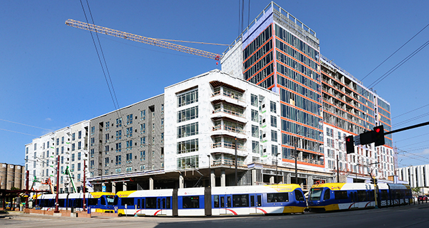 A Green Line light rail train travels in front of The Link at Prospect Park apartments under construction at 2929 University Ave. SE near the Prospect Park light rail station in Minneapolis. The 15-story market-rate building will include a Fresh Thyme grocery store. (Staff photo: Bill Klotz)