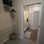 The bathroom of a one-bedroom apartment is connected to the bedroom by a walk-through closet.