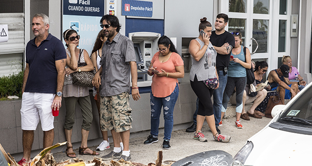 People stand in line Sept. 27, 2017 to withdraw cash from an ATM after Hurricane Maria heavily damaged the electricity system in San Juan, Puerto Rico. As early as the day after the storm, the Federal Reserve began working to get money onto the island. (Bloomberg photo: Alex Wroblewski)