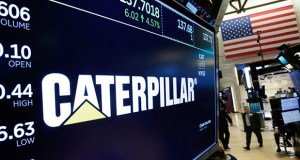 The logo for Caterpillar appears above a trading post on the floor of the New York Stock Exchange on Tuesday. Caterpillar Inc.'s third-quarter profit surged on demand for construction equipment, topping Wall Street expectations. (AP Photo: Richard Drew)