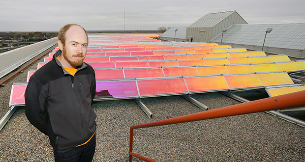 Max Currie, construction manager for Suntide Commercial Realty, stands with the photovoltaic array on the roof of the Court International building at 2550 University Ave. W. in St. Paul. (Staff photo: Bill Klotz)