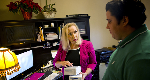 Gail Trauco, owner of The PharmaKon, left, talks Dec. 4 with Jordan Rubio, her office manager and son, while working in her home office in Peachtree City, Georgia. Trauco's insurer is eliminating her company's policy known as a preferred provider organization, or PPO, replacing it with a health maintenance organization, or HMO, a change that would limit the choice of doctors for her five employees. Her annual costs were scheduled to rise by nearly $10,000 in 2018. (AP Photo: David Goldman)