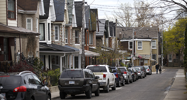 Vehicles sit parked outside houses in May 2017 in Toronto, Ontario. The city's housing market has cooled of late, with prices falling and listings surging. The market has begun to buckle under a raft of measures to curb prices that were soaring at a 20 percent clip a year ago. (Bloomberg file photo)