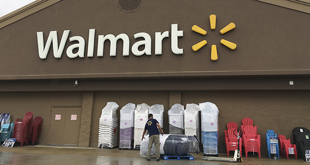 A worker stacks merchandise June 5, 2017, outside a Walmart in Salem, New Hampshire. (AP file photo)