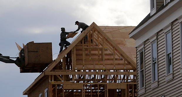 The National Association of Homebuilders cited higher building material costs and a lack of land to build on as key reasons for lower levels of confidence among homebuilders in March. In this photo, construction workers build a townhouse Feb. 26 in Wood-Ridge, New Jersey. (AP file photo)