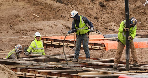 Concrete workers pour footings for The CAPP, a mixed-use building being developed by Oppidan in South Minneapolis at the intersection of 46th Street East and Hiawatha Avenue. The five-story building will have 148 market rate units above a Cub grocery store. (Staff photo: Bill Klotz)