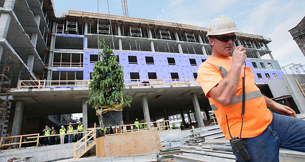 """Gresser Concrete employee Randy Root stands with the """"topping off"""" tree behind him on its way to the top of Dorothy Day Place. (Staff photo: Bill Klotz)"""