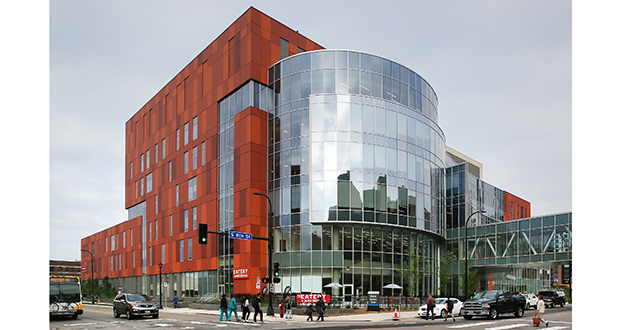 The new Hennepin County Healthcare Clinic and Specialty Center has a paneled façade in orange hues and a bending, window-filled entrance that dramatically punches up the neighborhood. (Staff photo: Bill Klotz)
