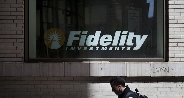 Fidelity Investments jump-started the no-fee push in August by offering index funds for free. This April 2012 photo shows a pedestrian passing a Fidelity Investments branch in New York. (Bloomberg file photo)