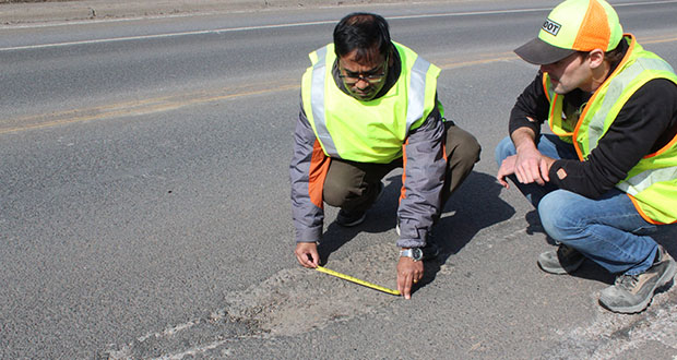 """Manik Barman, anassistant professor in theSwenson College of Science and Engineeringat the University of Minnesota Duluth, measures a pothole with UMD graduate student Jared Munch.""""There are five or six types of patching methods, so it's not like all those methods work for any all types of potholes,"""" Barman said. (Submitted photo: UMD)"""
