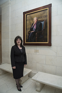 Kristine Kubes stands before the portrait of Justice Sandra Day O'Connor before being sworn into practice before the U.S. Supreme Court. (Submitted photo)