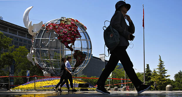 People walk by a globe structure showing the United States on display Monday outside a bank in Beijing. (AP Photo: Andy Wong)