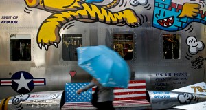 In this May 13 photo, a woman walks by a bench painted with an American flag outside a fashion boutique selling U.S. brand clothing at a popular shopping mall in Beijing. (AP file photo)