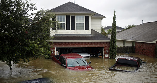 Since 1980, more than 241 billion-dollar disasters have cost the U.S. $1.6 trillion and almost half of those losses came during the four most expensive years: 2017, 2005, 2012 and 2018. This Aug. 28, 2017, photo shows houses and vehicles at the Highland Glen subdivision stand in floodwaters due to Hurricane Harvey in Spring, Texas. (Bloomberg file photo)