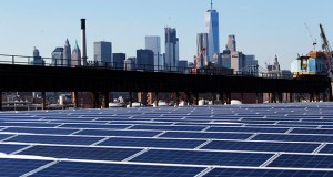 A rooftop is covered with solar panels at the Brooklyn Navy Yard in New York in this 2017 photo. The Manhattan skyline is at top. (AP file photo)
