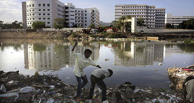 Children play at a garbage dump July 15 next to the polluted Cooum River, one of half a dozen natural waterways in Chennai, capital of the southern Indian state of Tamil Nadu. Rapid development and rampant construction have overtaxed a once-abundant natural water supply in Chennai. (AP Photo: Manish Swarup)