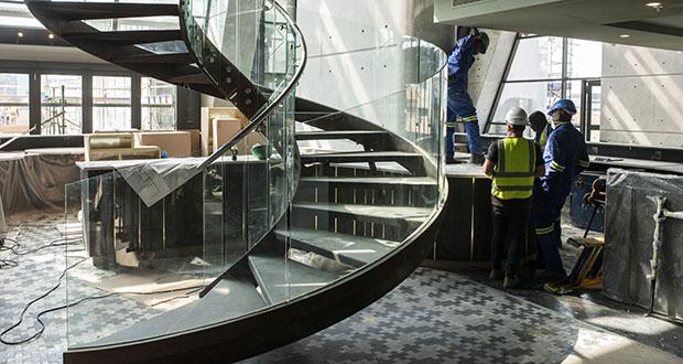 A glass-paneled spiral staircase leads between floors inside The Leonardo. (Bloomberg photo: Waldo Swiegers)