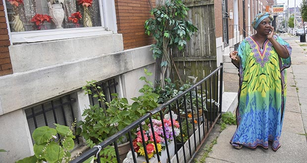 In this July 9 photo, Lorraine Diggs stands on the sidewalk outside her rowhouse in East Baltimore. Diggs is passionate about maintaining the trees outside of her home and has dedicated a small garden in front of her house to her late mother. Heat islands in cities tend to have more pavement and fewer trees to provide shade. (Photo: University of Maryland Capital News Service via AP)