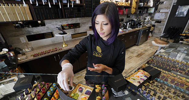 Annie Rupani, owner of Cacao & Cardamom, fills a custom box with chocolates Sept. 16 inside one her shops in Houston. She's seen the amount that people spend on each visit drop in the past year. Like many retailers, she's going to put more effort and investment into her online business. (AP Photo: David J. Phillip)