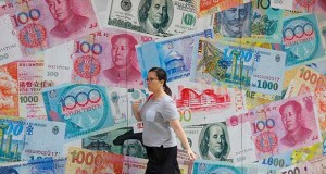 A woman walks by a money exchange shop decorated with different countries currency banknotes Aug. 6 at Central, a business district in Hong Kong. The IMF's latest World Economic Outlook comes on the eve of meetings in Washington this week of the IMF and its sister lending organization, the World Bank. (AP file photo)