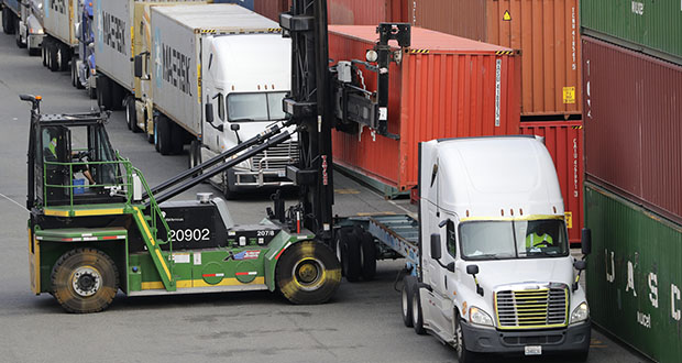 U.S. imports tumbled 1.7% to $254.3 billion on reduced purchases of foreign oil, cars and auto parts and pharmaceuticals. In this Oct. 2 photo, a shipping container is lifted off the back of a truck as others wait in line to have their cargo unloaded at a terminal on Harbor Island in Seattle. (AP file photo)