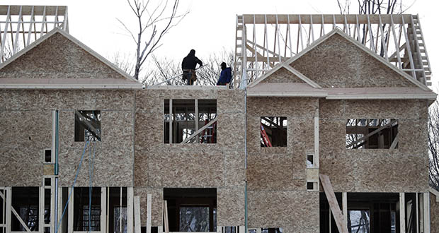 In this Jan. 23, 2019 photo, construction workers build new housing in Salisbury, Mass. (AP Photo/Elise Amendola)