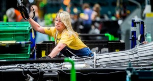 In this June 12, 2019, file photo General Motors employees work on the chassis line as they build the frame, power train and suspension onto the truck's body at the Flint Assembly Plant in Flint, Mich. (Jake May/The Flint Journal via AP, File)