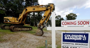 In this Sept. 3, 2019, file photo a sign rests near a piece of earth-moving equipment, left, on a plot of land, in Westwood, Mass. (AP Photo/Steven Senne, File)