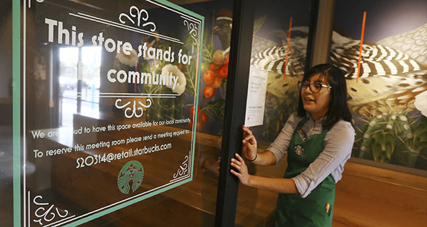 Belith Ariza, a barista trainer at Starbucks, opens the doors to the community meeting space at a local Starbucks Community Store on Jan. 15, in Phoenix. The Seattle-based company plans to open or remodel 85 stores by 2025 in rural and urban communities across the U.S. That will bring to 100 the total number of community stores Starbucks has opened since it announced the program in 2015. (AP Photo: Ross D. Franklin)