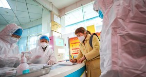 Medical workers in protective gear talk with a woman suspected of being ill with a coronavirus Monday at a community health station in Wuhan in central China's Hubei Province. China on Monday expanded sweeping efforts to contain a viral disease by extending the Lunar New Year holiday to keep the public at home and avoid spreading infection. (Photo: Chinatopix via AP)