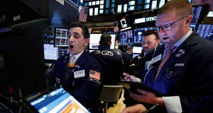 Specialist Peter Mazza, left, works with traders Monday at his post on the floor of the New York Stock Exchange. (AP Photo: Richard Drew)