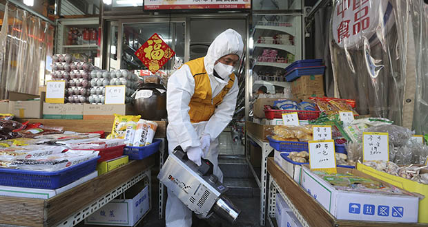 A worker wearing protective gears sprays disinfectant at a Chinese food store as a precaution against a new coronavirus Feb. 5 at Daelim market in Seoul, South Korea. (AP file photo)