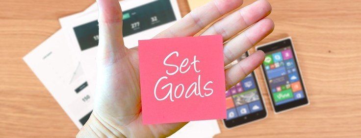 """Hand with a pink sticky note that says """"set goals"""""""