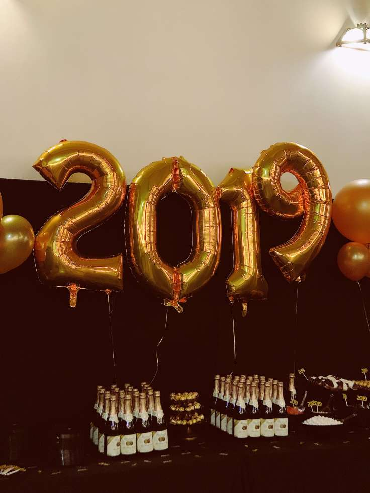 Balloons in the shape of 2019 in front of table with champagne bottles