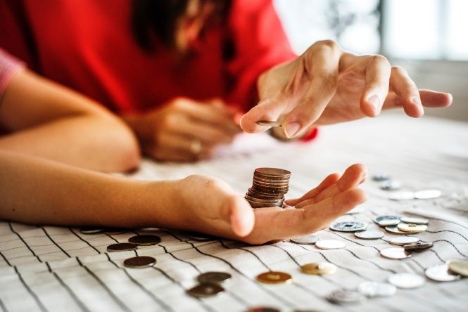 woman stacking pennies on a hand