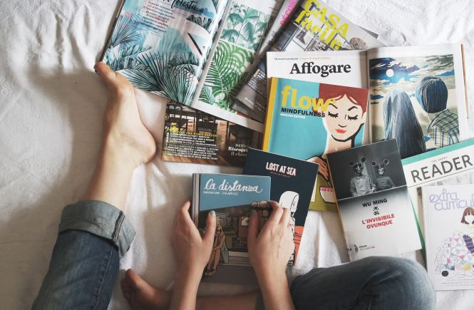 Woman surrounded by books on bed