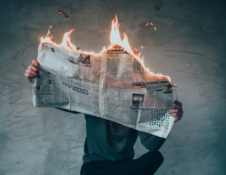 Person reading flaming newspaper