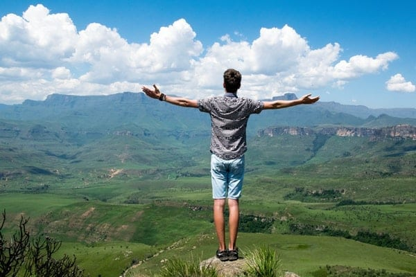 Photo of a man standing high on a mountain celebrating personal goals for 2019